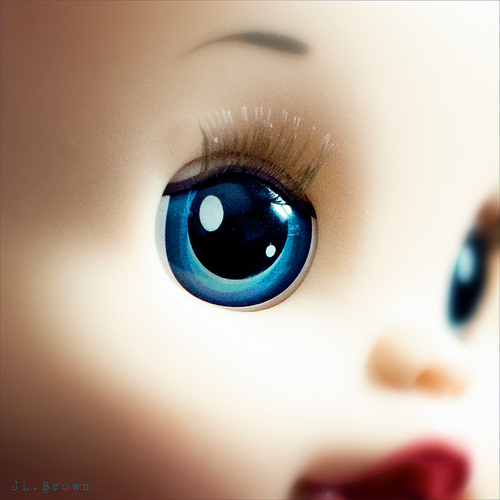 close-up photo of a doll with blue eyes