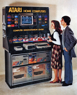 Retro image of young couple standing in front of a large Atari home computer