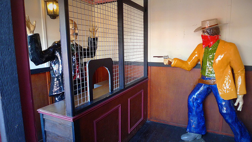 Robber figurine pointing gun at a bank teller figurine