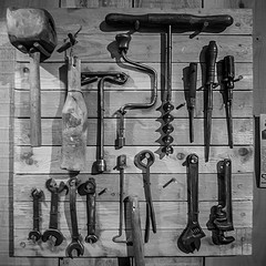 Black-and-white photo of tools hanging on a wall