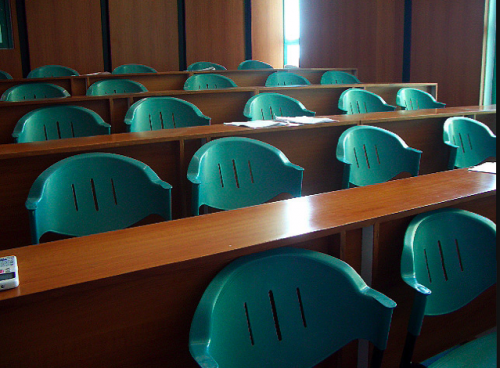 Tiered rows of green plastic chairs in a classroom