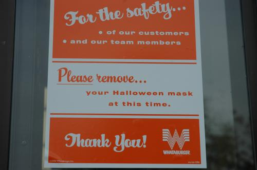 "This photograph zooms in on a white and orange Whataburger sign that reads, ""For the safety...of our customers and our team members. Please remove...your Halloween mask at this time. Thank You!"""