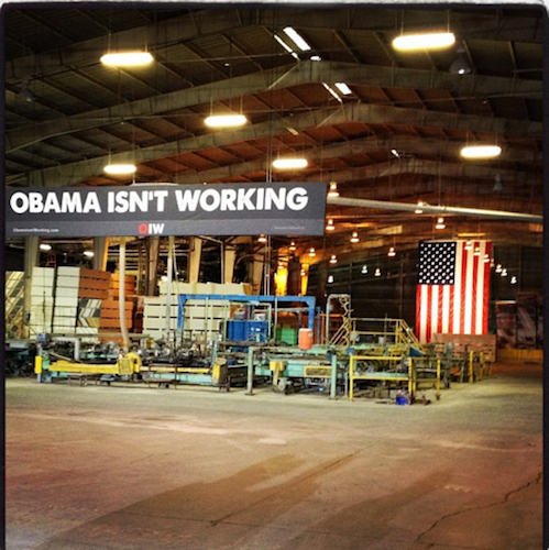 Sign reading Obama Isn't Working hangs in front of American flag in empty factory