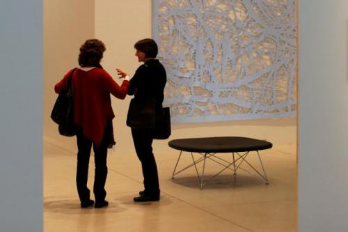 Two woman conversing in an art gallery