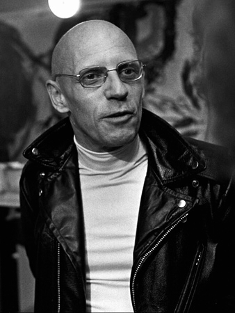 Black and white photo of Michel Foucault in a leather jacket