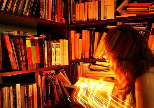 Standing among bookshelves, a woman holds an open book with bright lights shooting out of it