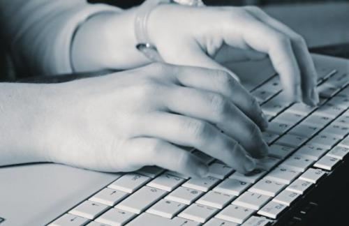 Black and white photo of hands typing